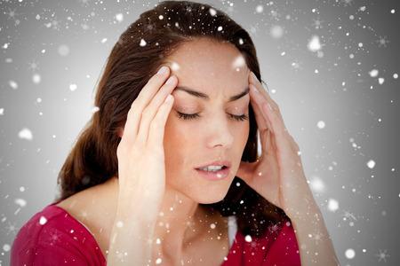 downcast: Composite image of beautiful woman having a headache against snow falling