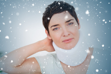Close up of a woman with a surgical collar against snow falling photo