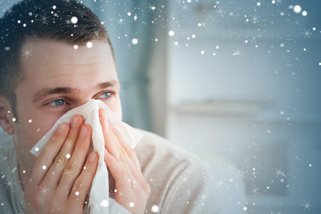 Composite image of sick man blowing his nose against snow photo