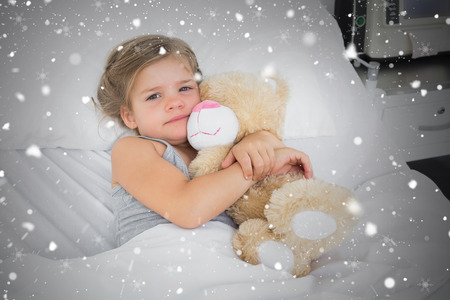 Composite image of cute girl embracing teddy bear in hospital bed against snow falling photo