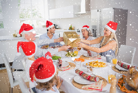 Composite image of Festive family exchanging gifts against snow falling photo