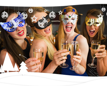 hedonism: Attractive friends with masks on holding champagne glasses against christmas themed frame Stock Photo