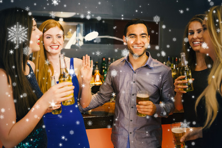 Composite image of Happy friends holding beers against snow falling photo