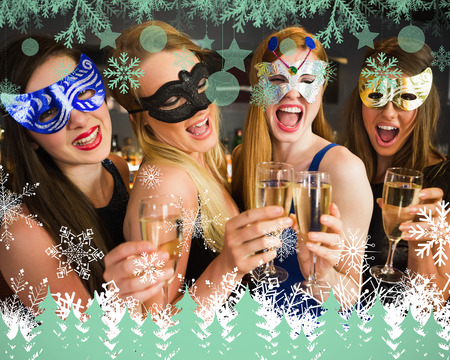Attractive friends with masks on holding champagne glasses against snowflakes and fir trees in green photo