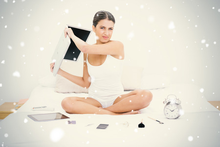 Furious young brown haired model in white pajamas throwing her laptop against snow falling photo