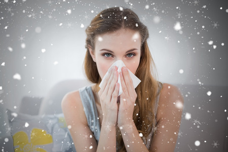 Sick young woman sitting on sofa blowing her nose against snow falling photo