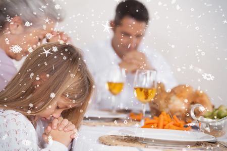 Composite image of Little girl saying grace with family  against snow falling photo