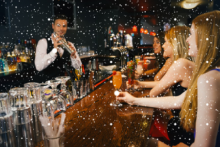 Handsome bartender making cocktails for attractive women against snow falling photo