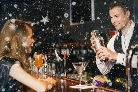 Handsome bartender serving cocktail to beautiful woman against snow photo