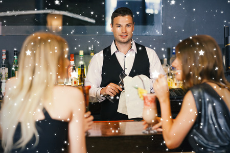 Handsome bartender working while gorgeous women talking against snow photo
