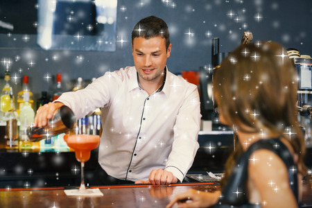 Handsome bartender serving cocktail to gorgeous woman against snow photo
