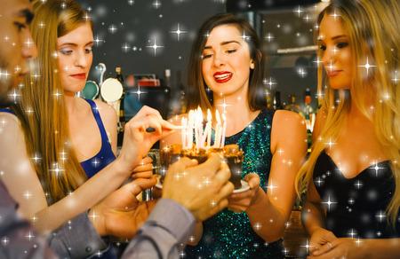 Composite image of Happy friends preparing birthday cake against snow photo