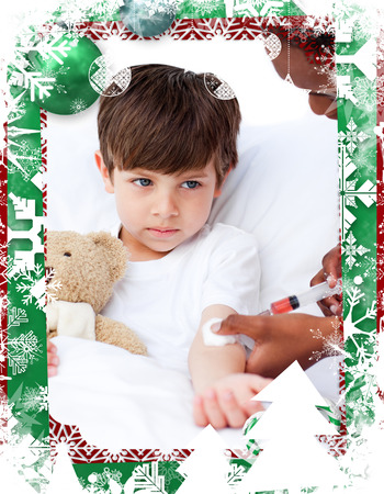 Sick little boy receiving an injection  against christmas themed frame photo