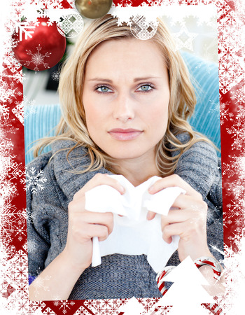 Diseased woman using a tissue sitting on a sofa against christmas themed frame photo