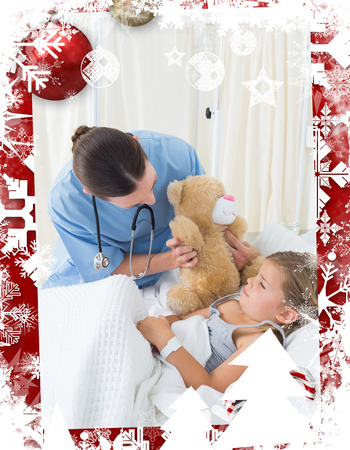 Doctor with teddy bear entertaining sick girl against christmas themed frame photo
