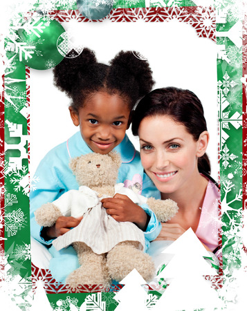Cute little girl with her doctor smiling at the camera  against christmas themed frame photo