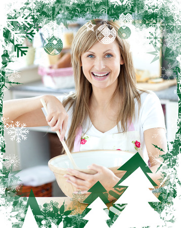 gratified: Close up of a woman preparing a cake in the kitchen against christmas themed frame