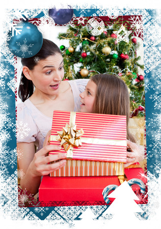 Mother and daughter at home at Christmas time against christmas themed frame photo