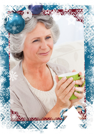 Senior drinking a cup of tea against christmas themed frame photo