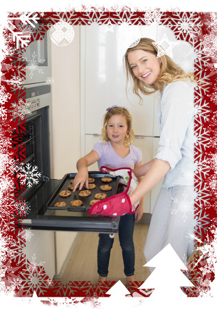 Woman baking cookies with daughter against christmas themed frame photo