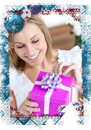 Delighted woman opening a gift sitting on the floor against christmas themed frame