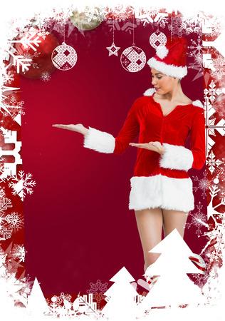 pere noel sexy: Jolie fille de Santa souriant � la cam�ra et de pr�senter contre le cadre sur le th�me de No�l Banque d'images