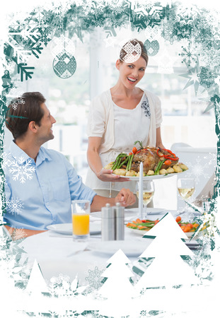 Attractive woman presenting a roast chicken against christmas themed frame photo