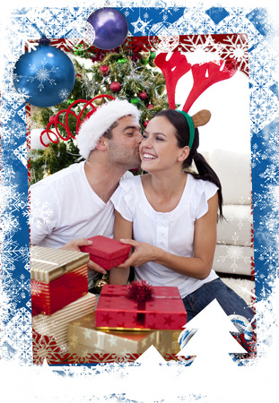 Lovely couple giving presents for Christmas against christmas themed frame photo