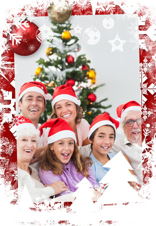 Happy family at christmas  against christmas themed frame photo