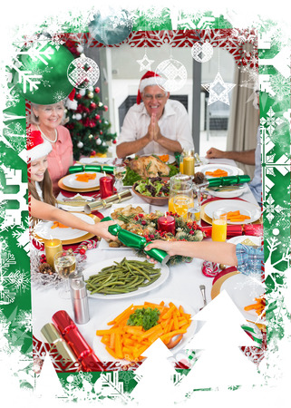 Cheerful family at dining table for christmas dinner against christmas themed frame photo