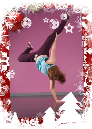 merry dancers: Pretty break dancer doing handstand with one hand against christmas themed frame Stock Photo