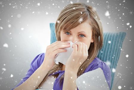 feeble: Portrait of a sick pretty woman blowing lying on a sofa against snow falling