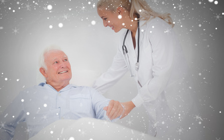 Composite image of doctor helping elderly man to sit up against snow photo