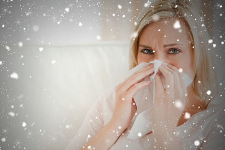 Composite image of sick woman blowing her nose against snow falling photo