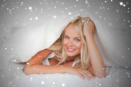 Composite image of smiling woman under a duvet against snow photo