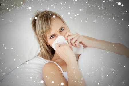 Composite image of sick blonde woman blowing lying on her bed against snow photo