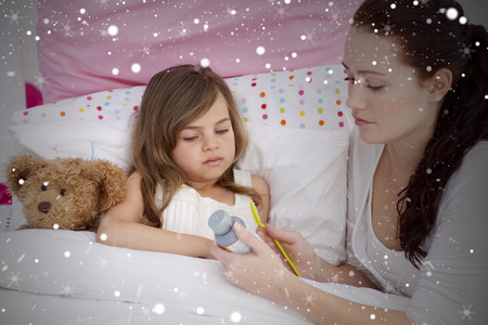 cough medicine: Composite image of mother giving her daughter cough medicine against snow