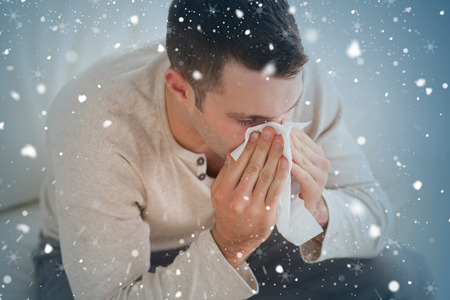 grippe: Composite image of ill man blowing his nose against snow falling