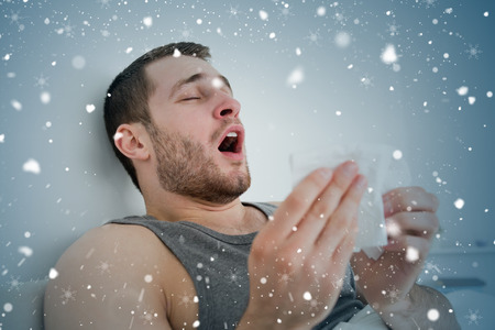 young  cuffs: Composite image of sick man sneezing against snow falling Stock Photo