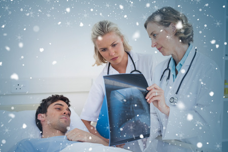 Composite image of doctors showing radiography to a patient against snow falling photo