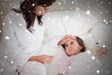 Composite image of mother checking on her daughters temperature against snow falling photo