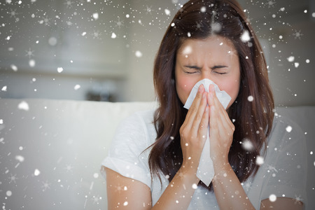 Composite image of brunette sneezing in a tissue against snow falling photo