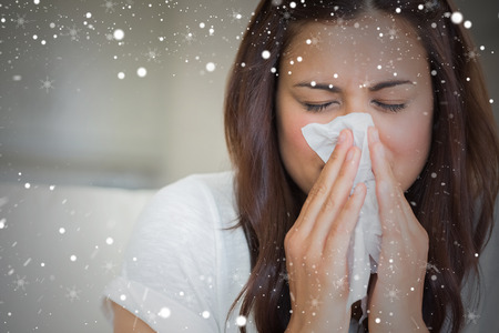 Composite image of brunette blowing nose into tissue against snow photo