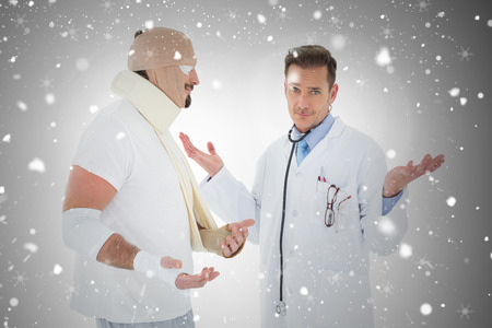 Portrait of a doctor with patient tied up in bandage against snow falling photo