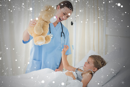 Composite image of doctor entertaining sick girl with teddy bear against snow photo