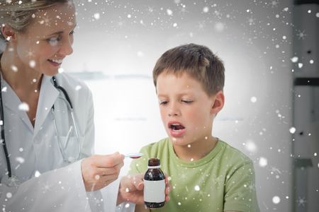 Doctor giving little boy cough syrup against snow falling photo