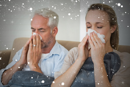 Composite image of sick couple blowing their noses sitting on the couch against snow photo