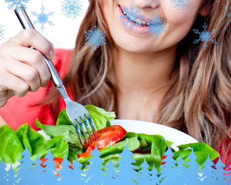 mirthful: Close up of a delighted woman is eating a salad  against snowflakes and fir trees in blue Stock Photo