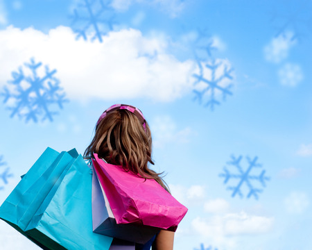 gratified: Composite image of woman holding shopping bags outdoor against snowflakes Stock Photo