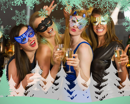Attractive women wearing masks holding champagne against snowflakes and fir tree in green